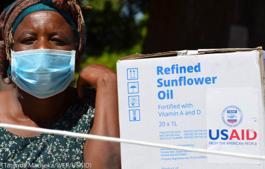 "Woman wearing mask next to box of sunflower oil marked ""USAID"" (Tatenda Macheka/WFP/USAID)"