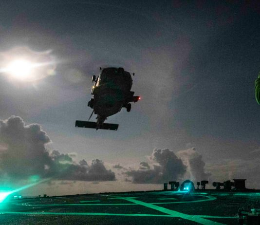 Helicopter landing on deck of ship at night (U.S. Navy/Mass Communication Specialist 2nd Class Markus Castaneda)
