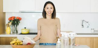 Sarah Paiji Yoo standing at kitchen counter with cleaning products (© Blueland)