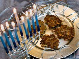 Les bougies bleues et blanches d'une menorah à côté de beignets de pommes de terre sur un plateau d'argent (© Larry Crowe/AP Images)