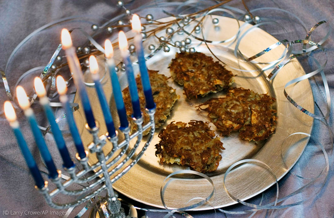 Blue-and-white candles in a menorah next to potato pancakes on a silver plate (© Larry Crowe/AP Images)