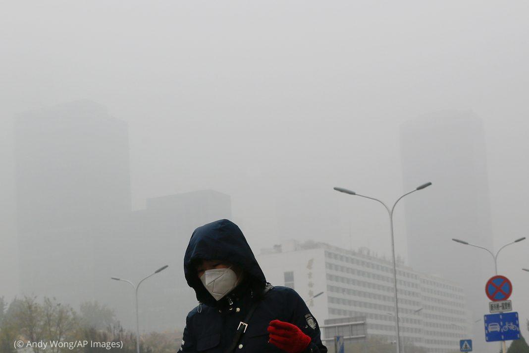 Женщина в маске, окруженная смогом, идет мимо здания (© Andy Wong/AP Images)