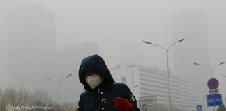 Woman in a mask walks in the smog in front of Beijing buildings (© Andy Wong/AP Images)
