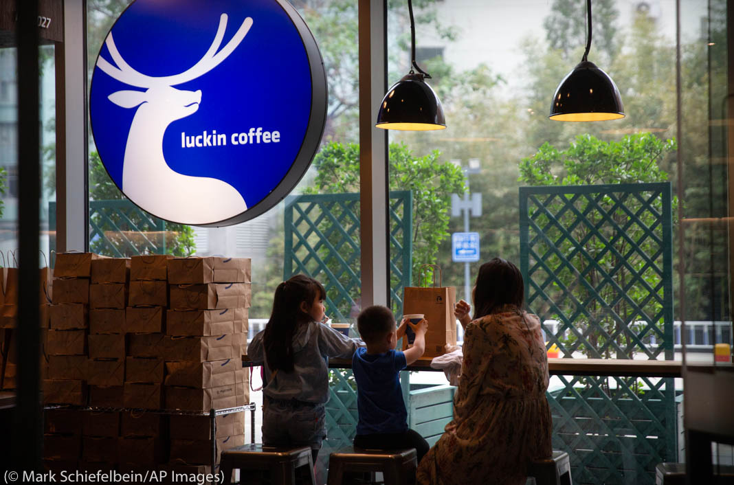 Woman and two children sitting inside a coffee shop underneath a round sign with a deer logo (© Mark Schiefelbein/AP Images)