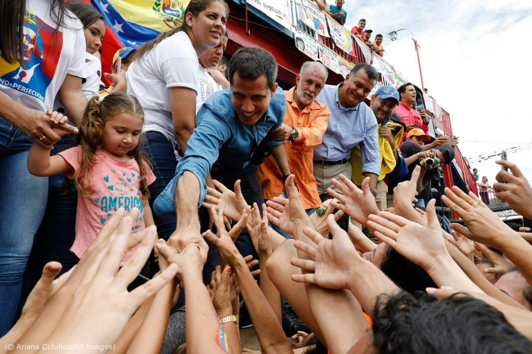 People extending their arms to shake hands with Juan Guaidó (© Ariana Cubillos/AP Images)