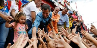 People extending their arms to shake hands with Guaido (© Ariana Cubillos/AP Images)