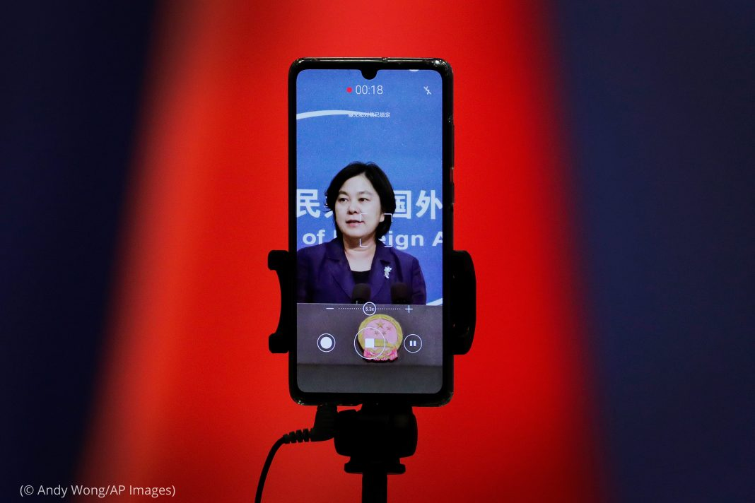 Smart phone recording a woman (© Andy Wong/AP Images)