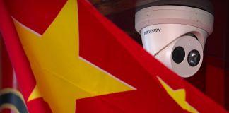 العلم الصيني معلق بالقرب من كاميرا مراقبة مثبتة على سقف (© Mark Schiefelbein/AP Images)