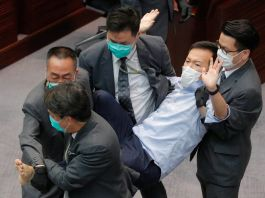 Security guards forcefully carry then-lawmaker Ray Chan out of a legislative meeting (© Kin Cheung/AP Images)