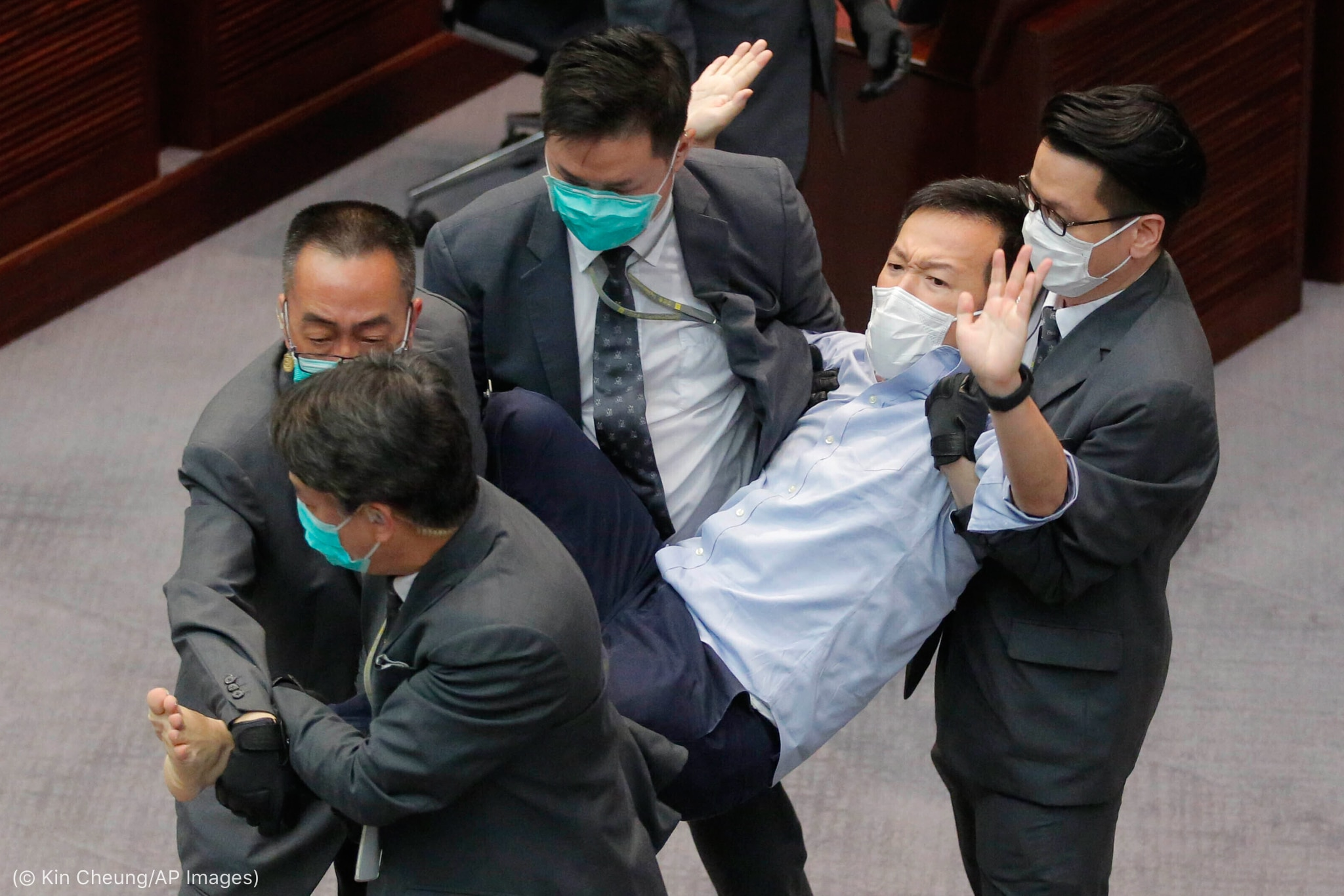 Four suited men carrying man (© Kin Cheung/AP Images)
