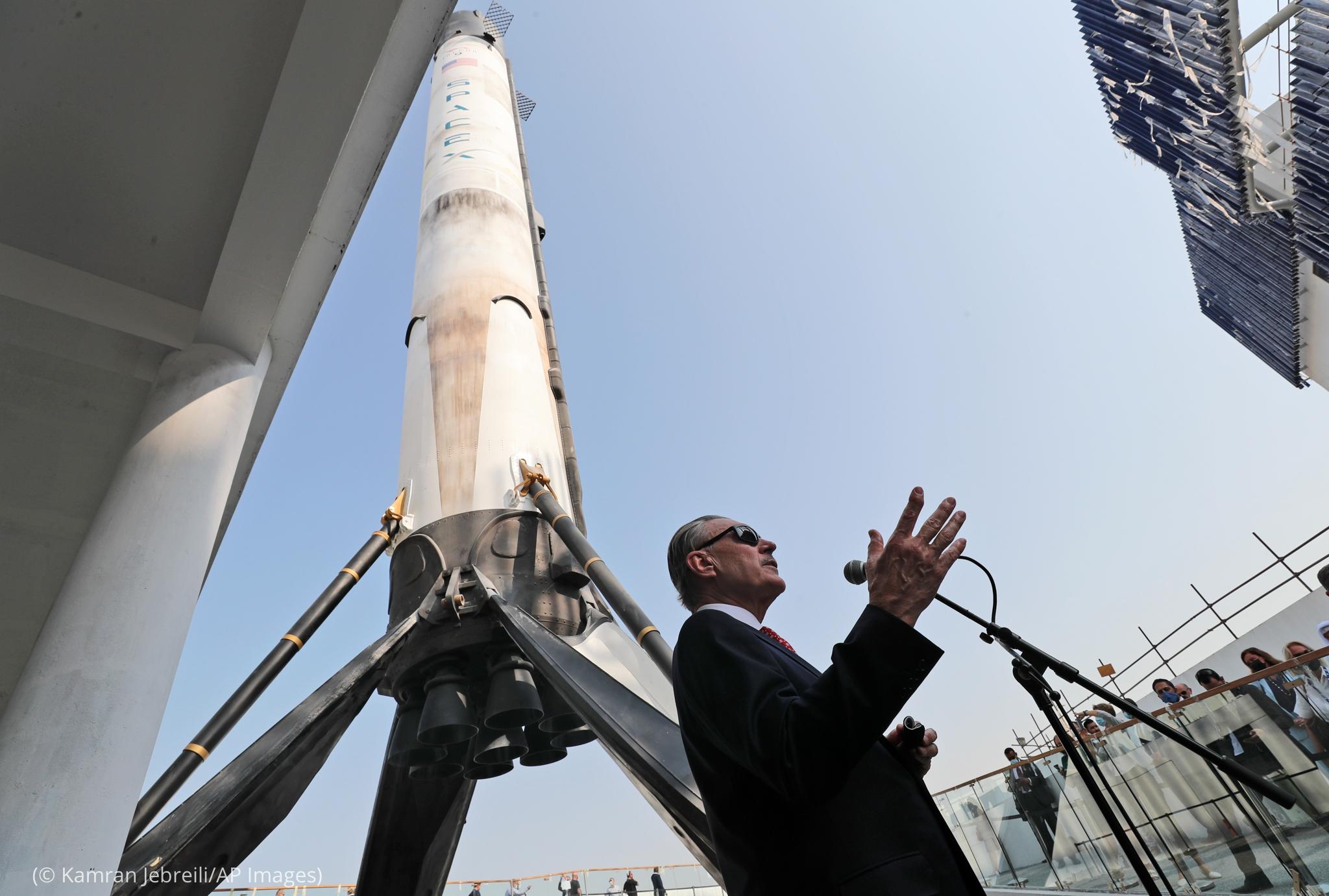 Man speaking in front of rocket replica (© Kamran Jebreili/AP Images)