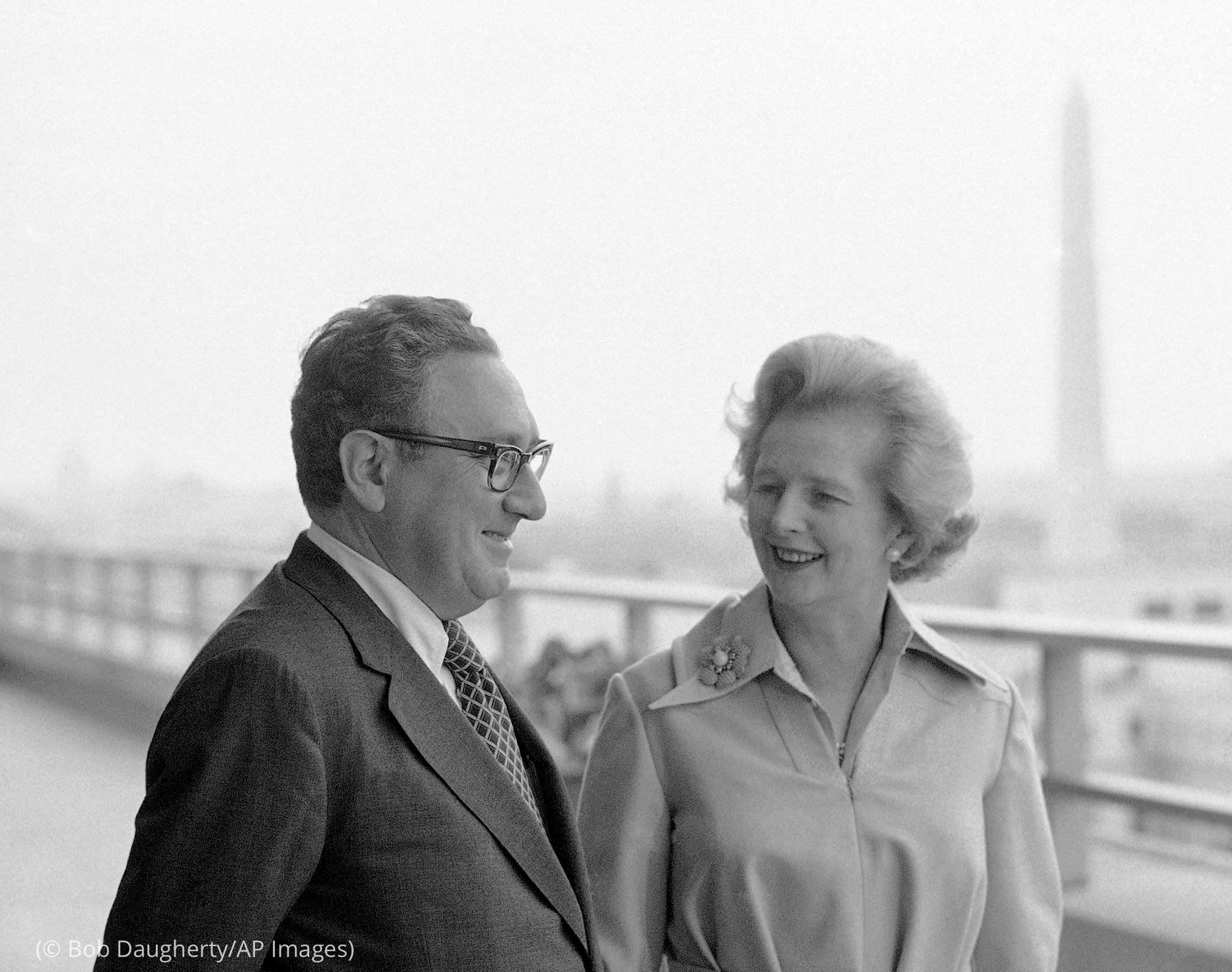 مارگریٹ تھیچر اور ہنری کسنجر عمارت کی چھت پر کھڑے ہیں اور پس منظر میں واشنگٹن کی یادگار دکھائی دے رہی ہے (© Bob Daugherty/AP Images)