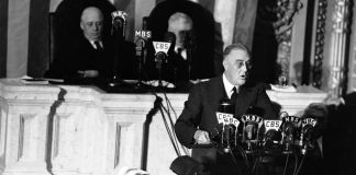 Franklin Delano Roosevelt at lectern with many microphones as two men sit behind him (© AP Images)