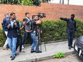 Masked man pointing at journalists with cameras on sidewalk (© AFP/Getty Images)