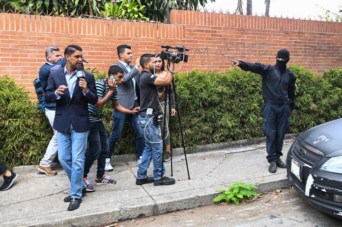 Masked man dressed up in black pointing his finger toward journalists with cameras on a sidewalk (© AFP/Getty Images)