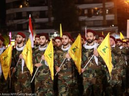 Men in camouflage uniforms carrying yellow flags (© Anwar Amro/AFP/Getty Images)
