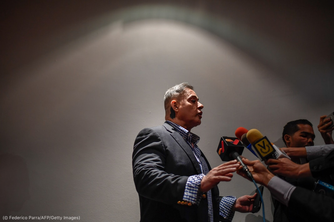 Tarek Saab speaking to people holding microphones (© Federico Parra/AFP/Getty Images)