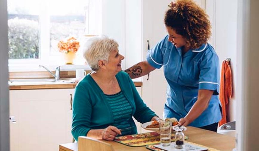 家政护理在照料一位老人的饮食起居(美国国立卫生研究院网站截图)