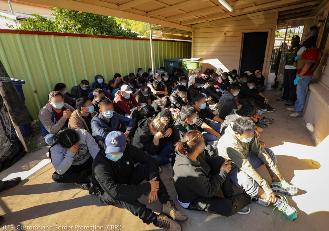 Illegal immigrants being detained outside of a stash house (Custom Border Patrol)