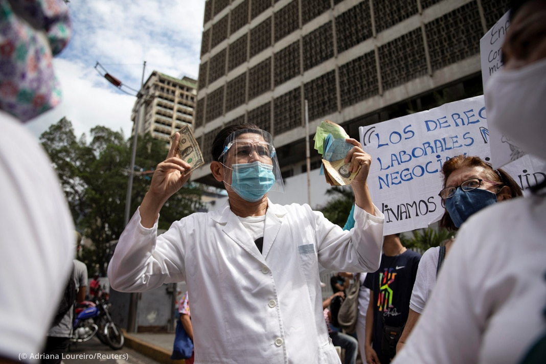 People wearing medical coats and protective equipment holding money and signs in street (© Adriana Loureiro/Reuters)