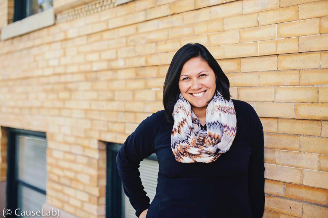 Mulher sorrindo na frente de parede de tijolos (© Causelab)
