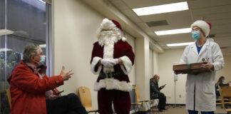 2020年圣诞节前一天,在旧金山南边戴利市(Daly City)的塞顿医疗中心(Seton Medical Center),身着红色上衣的詹姆斯·雷诺兹医生(. James Reynolds)在接受辉瑞的第一剂新冠疫苗注射之后,与另外两名医生交谈,其中一位医生打扮成圣诞老人。(美联社图片)