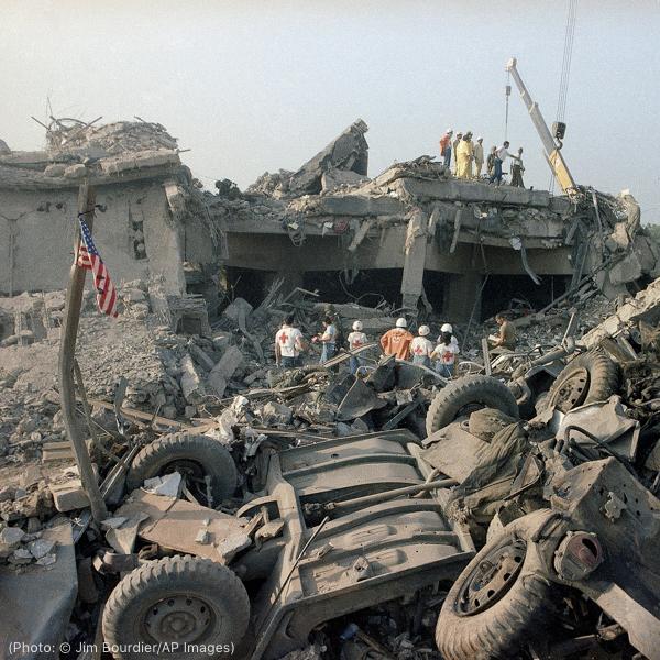 爆炸现场的废墟附近穿戴着红十字会标识的人们和吊车(© Jim Bourdier/AP Images)
