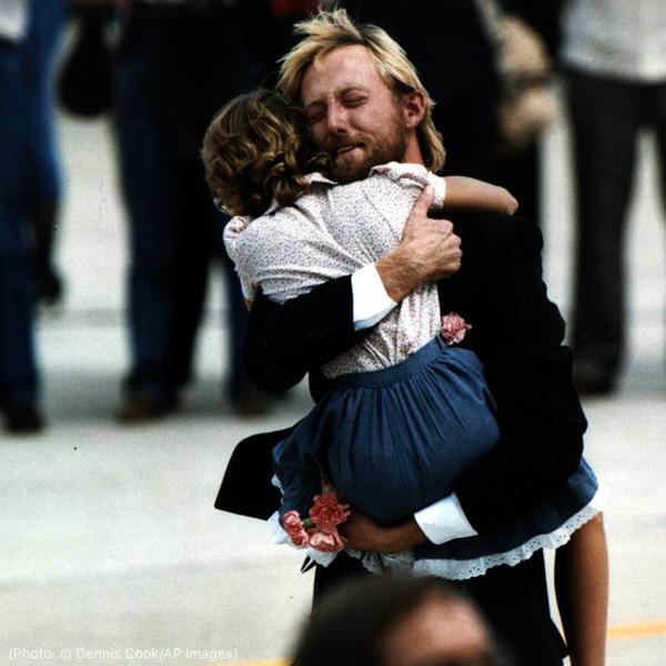 一名男子拥抱一名儿童(© Dennis Cook/AP Images)