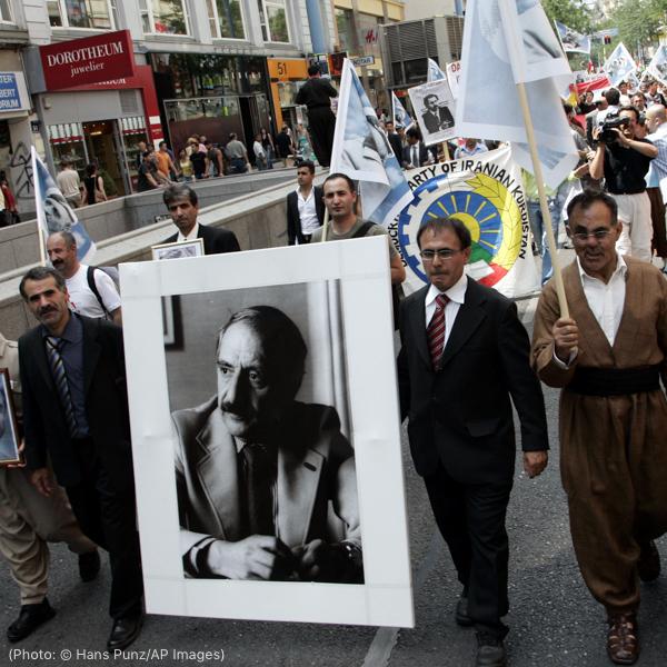 人们举着画像和旗帜走上街头(© Hans Punz/AP Images)