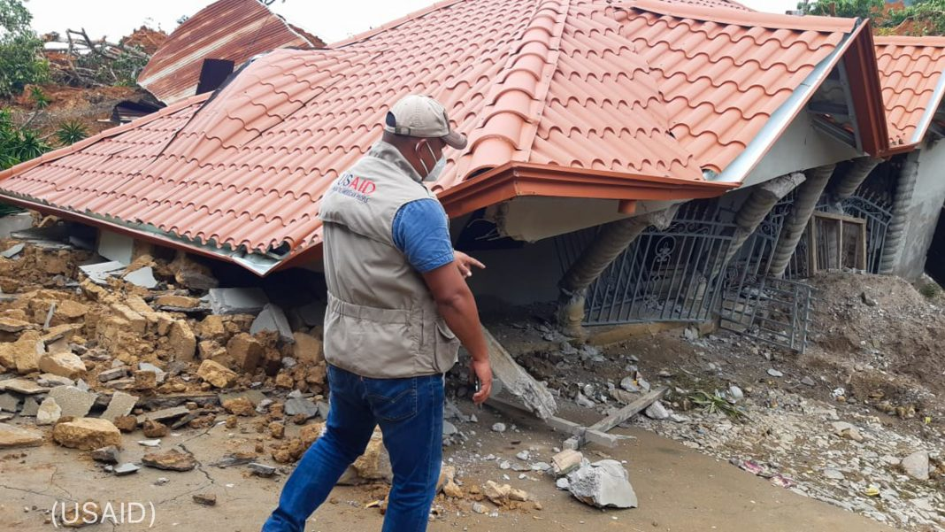 Man walking past destroyed home (USAID)