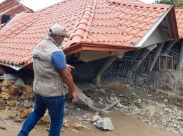 Man walking past a destroyed home (USAID)
