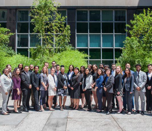 Sekelompok laki-laki dan perempuan berdiri di luar gedung Departemen Luar Negeri (State Dept.)