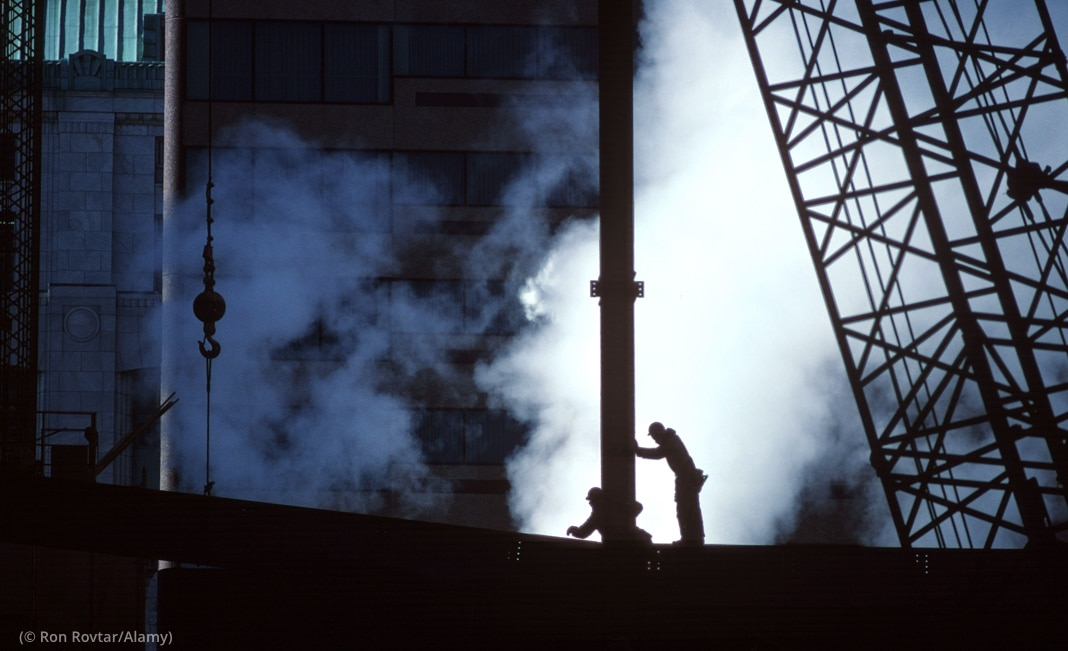 Construction workers silhouetted against rising steam, next to large crane (© Ron Rovtar/Alamy)