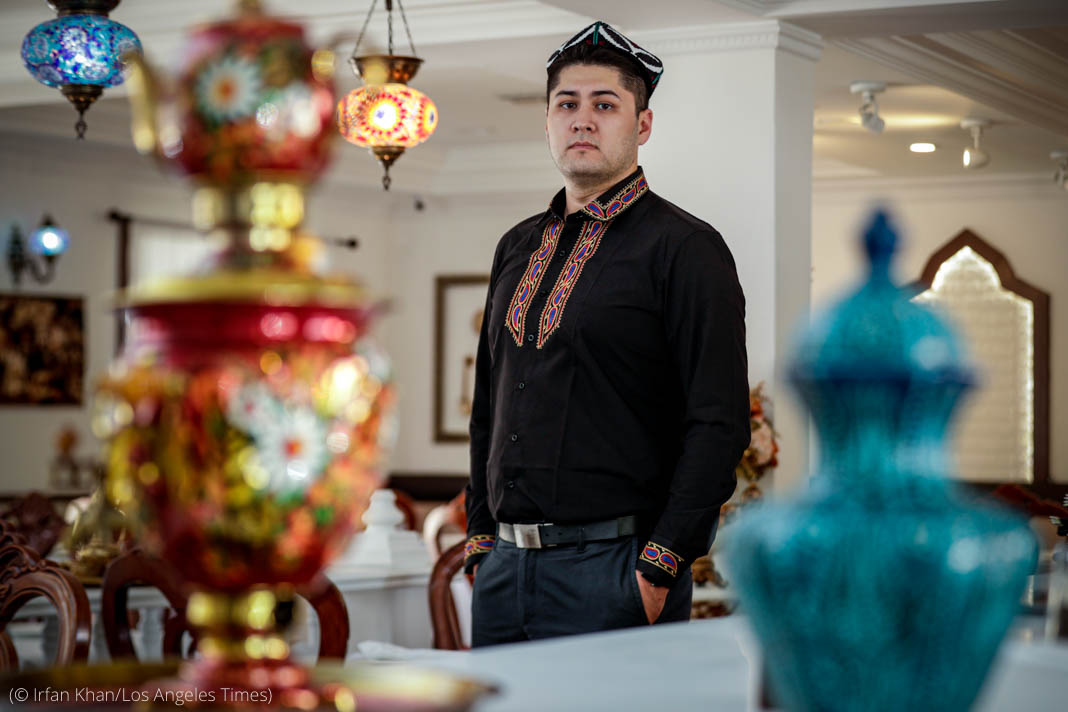 Man in embroidered shirt and hat standing behind elaborately decorated containers (© Irfan Khan/Los Angeles Times)