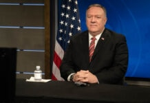 Mike Pompeo sitting at desk in front of screen and flag (State Dept./Freddie Everett)
