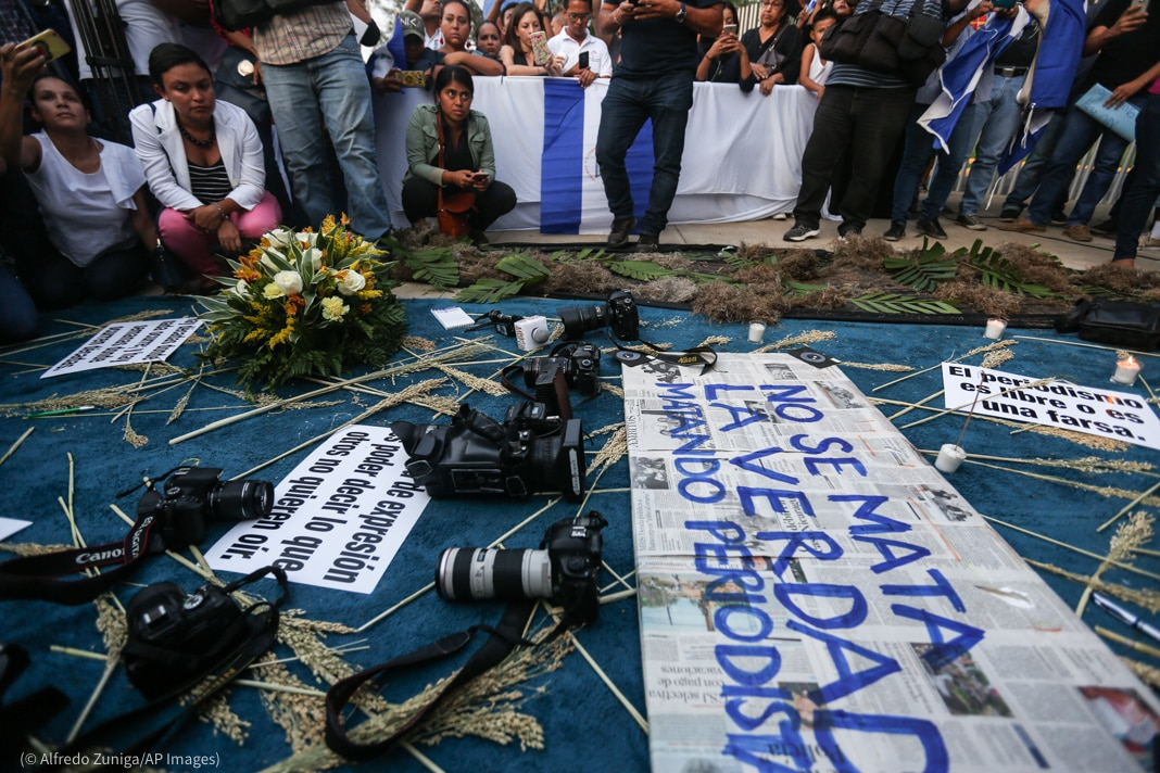 People sitting around signs and cameras placed on the ground (© Alfredo Zuniga/AP Images)