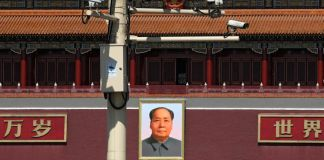 Security cameras on pole above photo of Mao Zedong (© Andy Wong/AP Images)