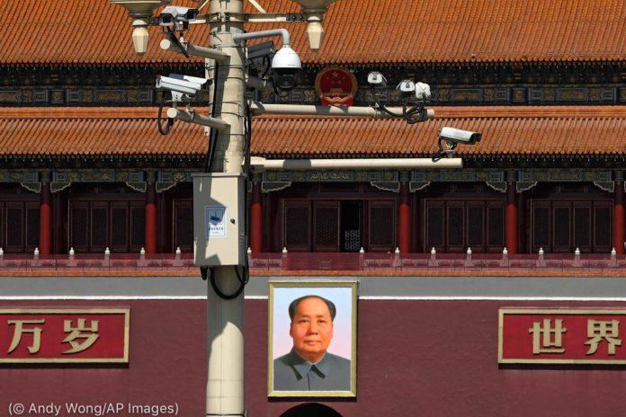 كاميرات الأمن على عمود فوق صورة ماو تسي تونغ (© Andy Wong/AP Images)