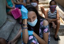 Woman wearing mask and gloves sitting among a group of people outside (© Ariana Cubillos/AP Images)