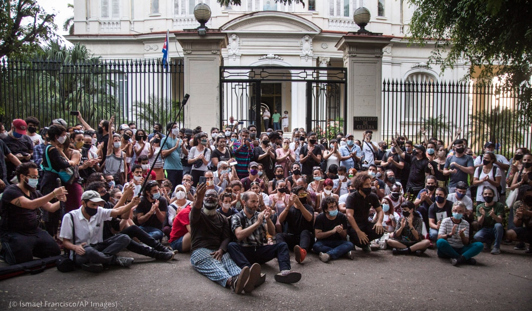 Large group of people sitting outside a gated building (© Ismael Francisco/AP Images)