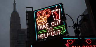A billboard with 'Take Out To Help Out' in neon lights (© Mark Lennihan/AP Images)