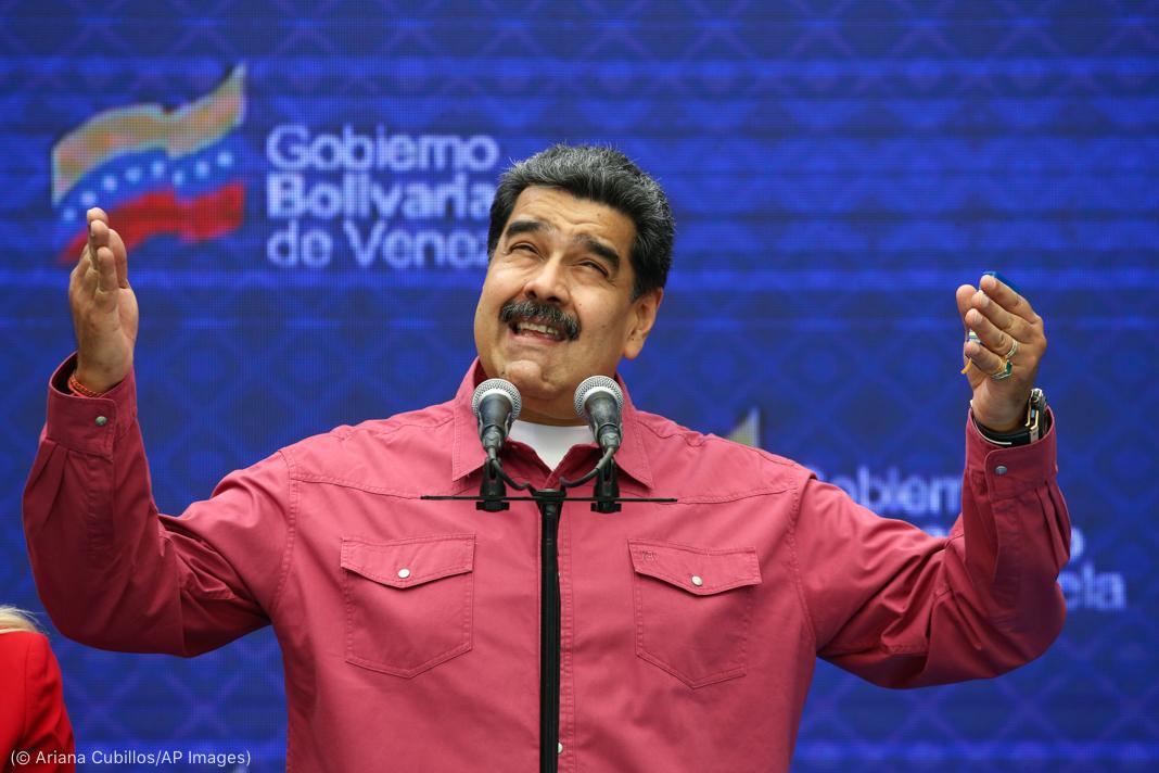Maduro ante un micrófono, mirando hacia arriba con los brazos levantados (© Ariana Cubillos/AP Images)