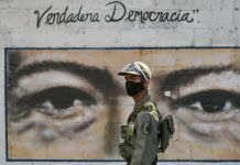 Soldier in uniform walking past mural showing the eyes of chavez (© Matias Delacroix/AP Images)