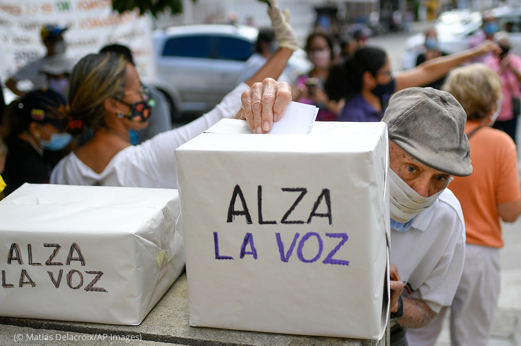 Man puts piece of paper into box while others stand behind him (© Matias Delacroix/AP Images)