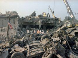 Personas con emblemas de la Cruz Roja y grúas cerca de escombros en el lugar de una explosión (© Jim Bourdier/AP Images)