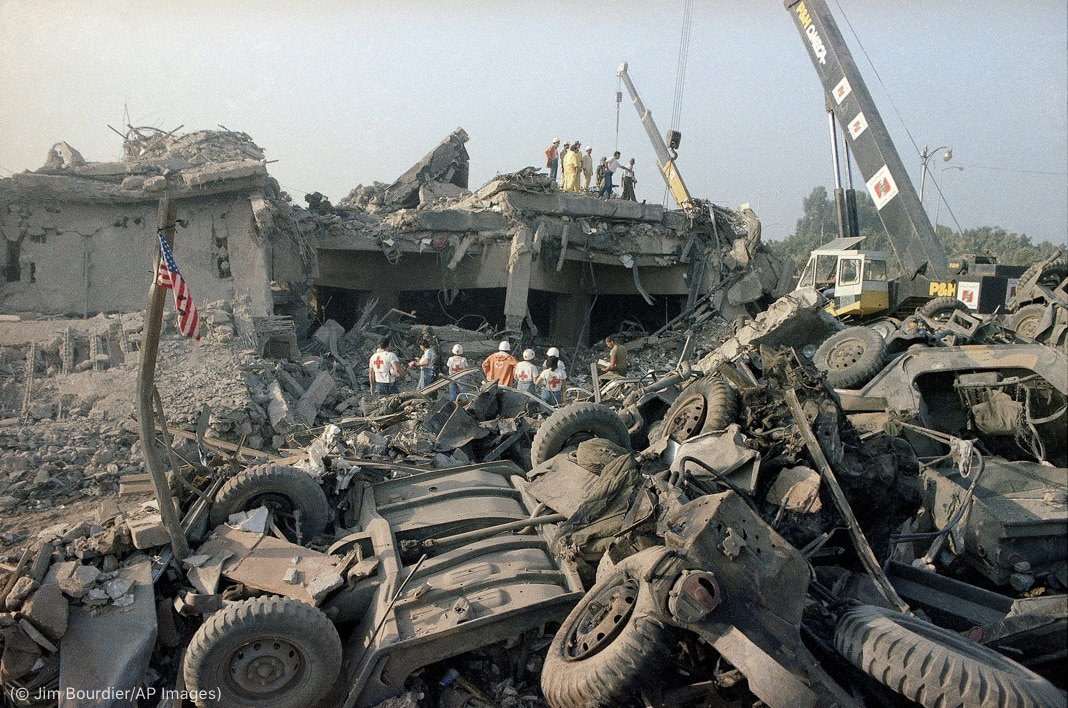 People wearing Red Cross emblems and cranes near rubble at blast site (© Jim Bourdier/AP Images)