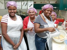 Women in aprons smiling in kitchen, with one using hand mixer in bowl (© Geovanni Hernandez/AES)