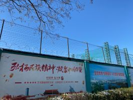 High fence with barbed wire and large Chinese posters (© Anna Fifield/The Washington Post/Getty Images)