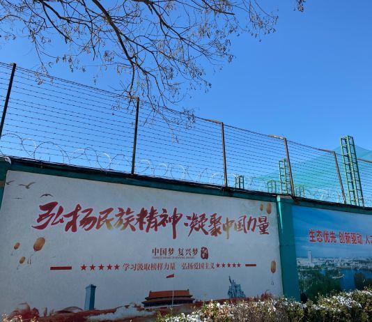 اونچی خاردار تاریں اور بڑے بڑے چینی پوسٹر (© Anna Fifield/The Washington Post/Getty Images)