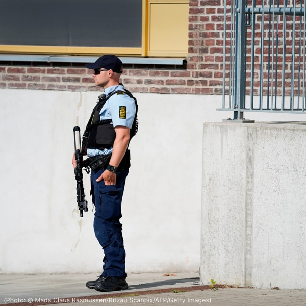 Police officer with weapon standing near building (© Mads Claus Rasmussen/Ritzau Scanpix/AFP/Getty Images)
